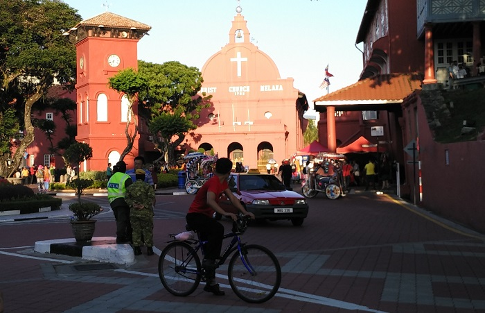 A cyclist outside Christ Church Melaka