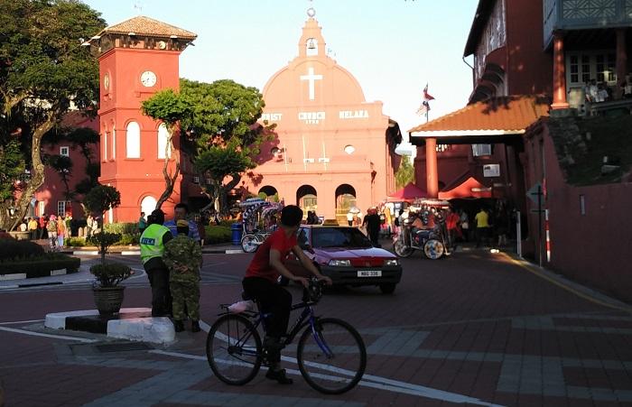 A cyclist outside Christ Church Melaka