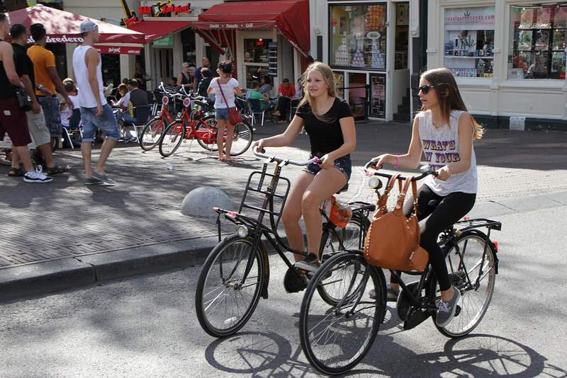 Two girls cycling in Amsterdam