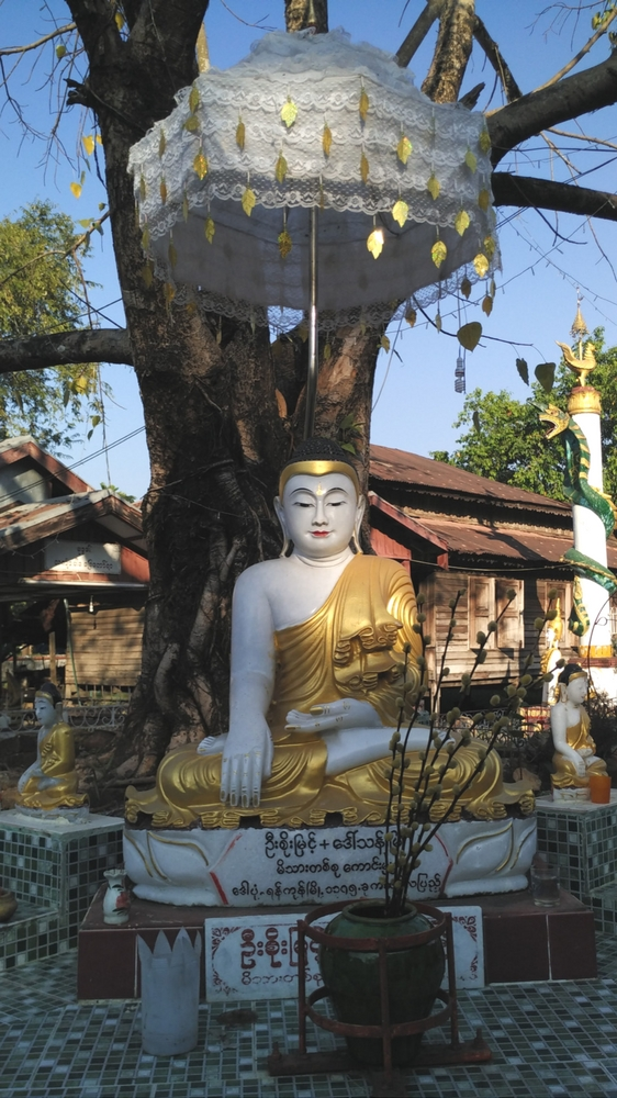A Buddha statue under a tree inside a monastery in Dala Village near Yangon, Myanmar