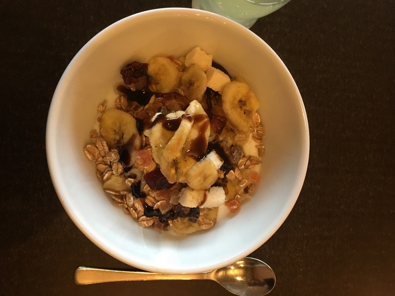 Muesli bowl with yoghurt, fried bananas, nuts, maple syrup, honey and more