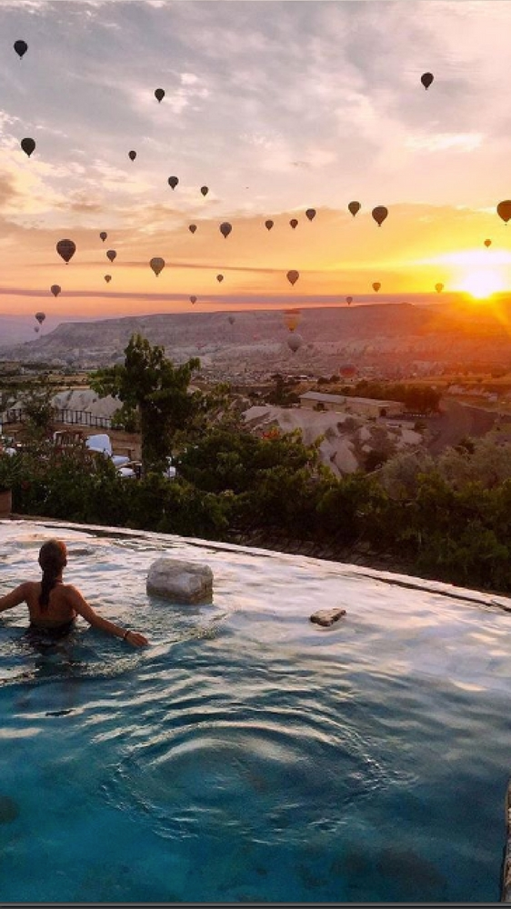 Swimming pool with a view of hot air balloons in Cappadocia, Turkey