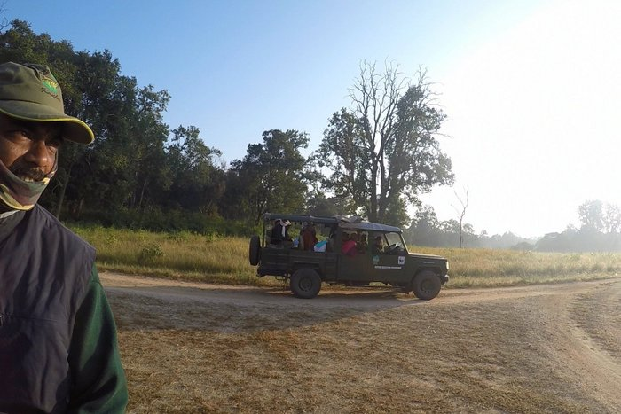 Our Naturalist and a safari jeep in the background in Kanha National Park, MP