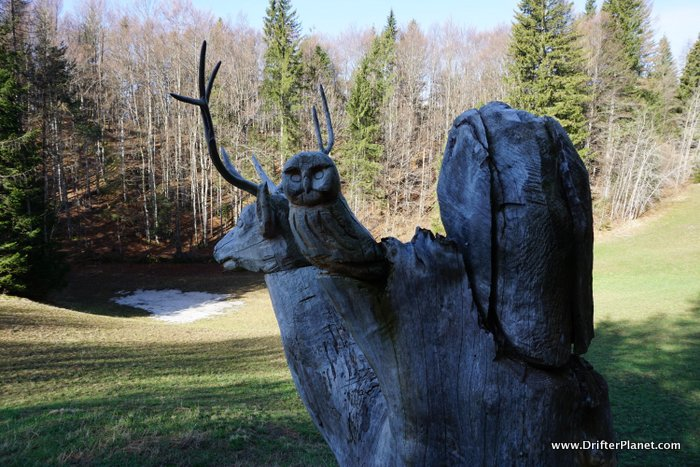 Wooden sculptures depicting the forest on Il Respiro Degli Alberi hiking trail in Alpe Cimbra, Trentino, Italy