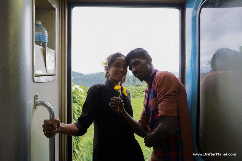 An adorable local couple enjoying the door seat - train ride in Sri Lanka
