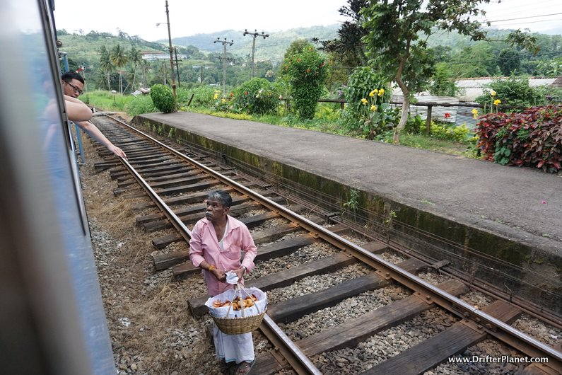 Buying snacks through the train window near Kandy, Sri Lanka