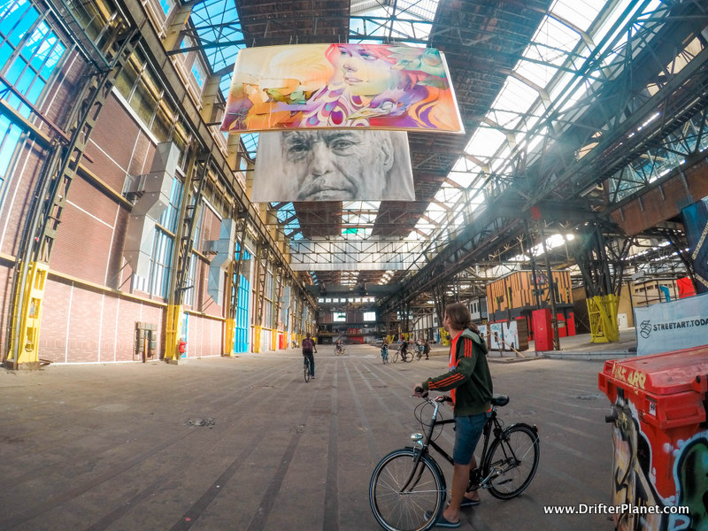 San with his bicycle admiring the artwork inside NDSM Werf in Amsterdam