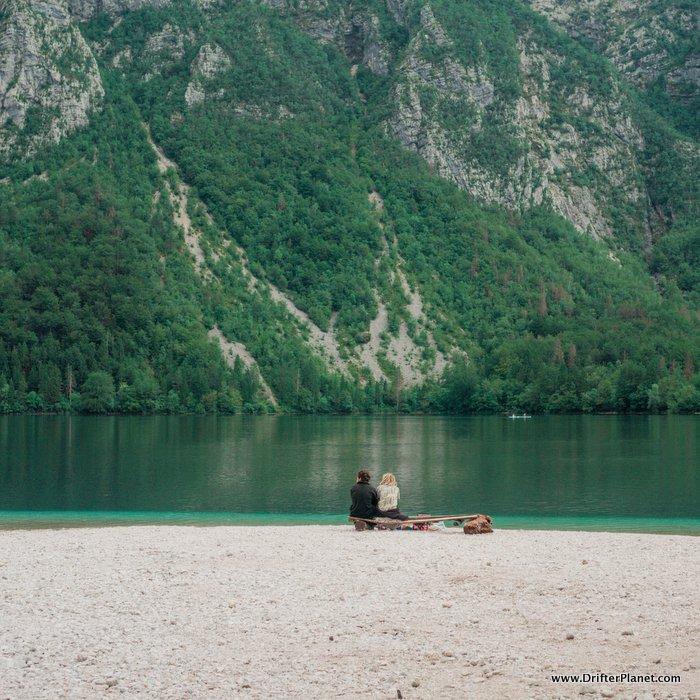 A couple on the beach by Lake Bohinj, Triglav National Park, Slovenia